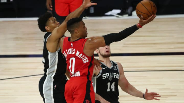 LAKE BUENA VISTA, FLORIDA - AUGUST 11: Russell Westbrook #0 of the Houston Rockets goes up for a shot against Keldon Johnson #3 of the San Antonio Spurs during the first half of a NBA basketball game at The Field House at ESPN Wide World Of Sports Complex on August 11, 2020 in Lake Buena Vista, Florida. NOTE TO USER: User expressly acknowledges and agrees that, by downloading and or using this photograph, User is consenting to the terms and conditions of the Getty Images License Agreement. (Photo by Kim Klement-Pool/Getty Images)