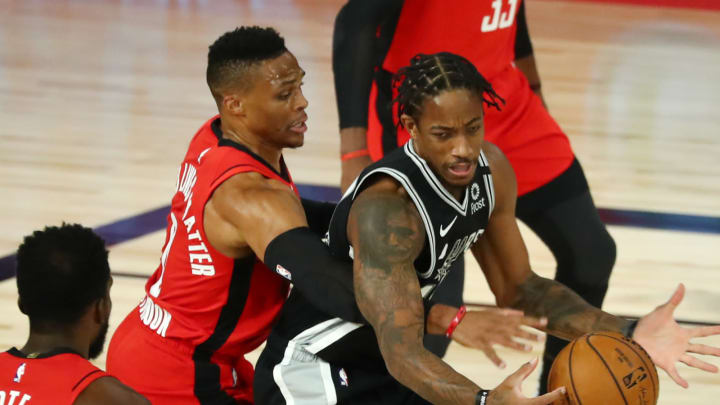 LAKE BUENA VISTA, FLORIDA – AUGUST 11: Russell Westbrook #0 of the Houston Rockets reaches for the ball against DeMar DeRozan #10 of the San Antonio Spurs at The Field House. (Photo by Kim Klement-Pool/Getty Images)