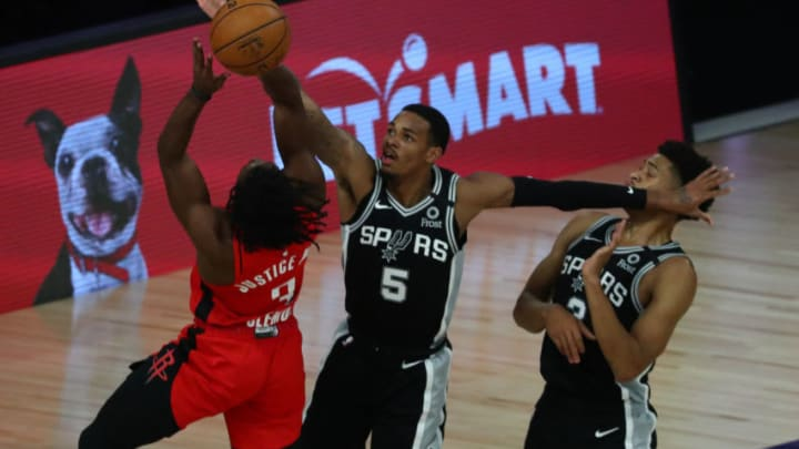 LAKE BUENA VISTA, FLORIDA - AUGUST 11: Dejounte Murray #5 of the San Antonio Spurs defends against Chris Clemons #3 of the Houston Rockets during the second half of a NBA basketball game at The Field House at ESPN Wide World Of Sports Complex on August 11, 2020 in Lake Buena Vista, Florida. NOTE TO USER: User expressly acknowledges and agrees that, by downloading and or using this photograph, User is consenting to the terms and conditions of the Getty Images License Agreement. (Photo by Kim Klement-Pool/Getty Images)