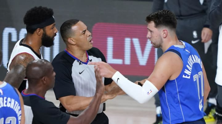 LAKE BUENA VISTA, FLORIDA - AUGUST 21: Officials get between Luka Doncic #77 of the Dallas Mavericks and Marcus Morris Sr. #31 of the LA Clippers during the first half of Game Three of the first round of the playoffs at the AdventHealth Arena at the ESPN Wide World Of Sports Complex on August 21, 2020 in Lake Buena Vista, Florida. NOTE TO USER: User expressly acknowledges and agrees that, by downloading and or using this photograph, User is consenting to the terms and conditions of the Getty Images License Agreement. (Photo by Ashley Landis-Pool/Getty Images)