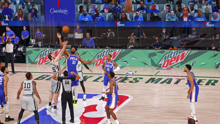 LAKE BUENA VISTA, FLORIDA – AUGUST 03: Jakob Poeltl #25 of the San Antonio Spurs and Joel Embiid #21 of the 76ers jump for the opening tip at Visa Athletic Center at ESPN Wide World Of Sports. (Photo by Mike Ehrmann/Getty Images)