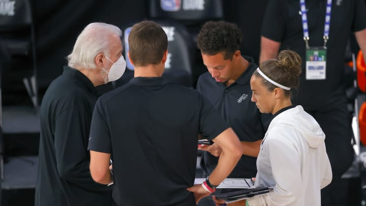 LAKE BUENA VISTA, FLORIDA – AUGUST 03: Head coach Gregg Popovich of the San Antonio Spurs speaks to his staff during a timeout against the Philadelphia 76ers at Visa Athletic Center. (Photo by Mike Ehrmann/Getty Images)