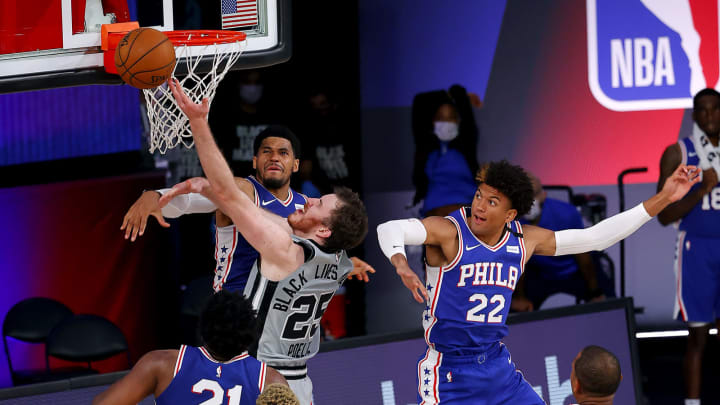 LAKE BUENA VISTA, FLORIDA – AUGUST 03: Jakob Poeltl #25 of the San Antonio Spurs misses against Tobias Harris #12 and Matisse Thybulle #22 of the Philadelphia 76ers at Visa Athletic Center. (Photo by Mike Ehrmann/Getty Images)