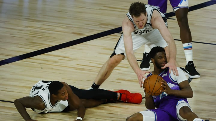 LAKE BUENA VISTA, FLORIDA – AUGUST 07: Jakob Poeltl #25 of the San Antonio Spurs reaches to steal the ball from Tony Bradley #13 of the Utah Jazz during the second quarter at HP Field House. (Photo by Kevin C. Cox/Getty Images)