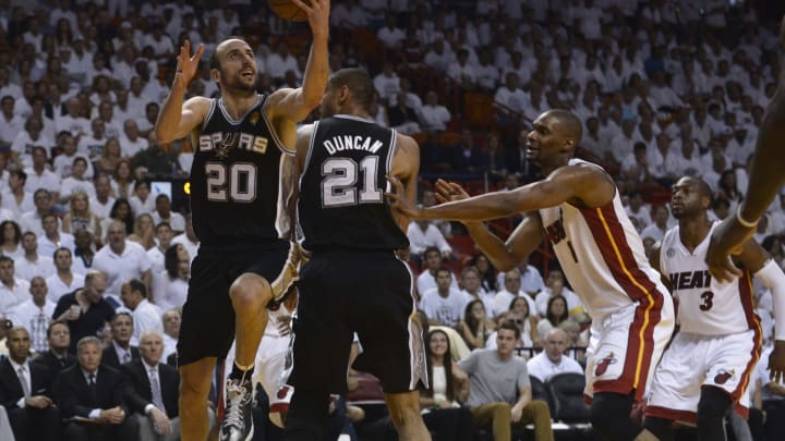 Manu Ginobili (L) of the San Antonio Spurs goes for the lay-up protected by teammate Tim Duncan as Chris Bosh (R) of the Miami Heat looks on during Game 7 of the 2013 NBA Finals (BRENDAN SMIALOWSKI/AFP via Getty Images)