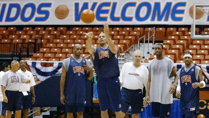 US player Jason Kidd (C) gets the attention of his teammates Allen Iverson (R), Ray Allen (2R), Vince Carter (2L) and assistant coach Gregg Popovich (3R) as he shoots a long distance shot at the end of their practice session at the Roberto Clemente Coliseum 19 August 2003 in San Juan, Puerto Rico. Team USA will be playing nine other teams during a 12-day tournament in which the first three placements will qualify for the Athens 2004 Olympics. AFP PHOTO/Roberto SCHMIDT (Photo credit should read ROBERTO SCHMIDT/AFP via Getty Images)