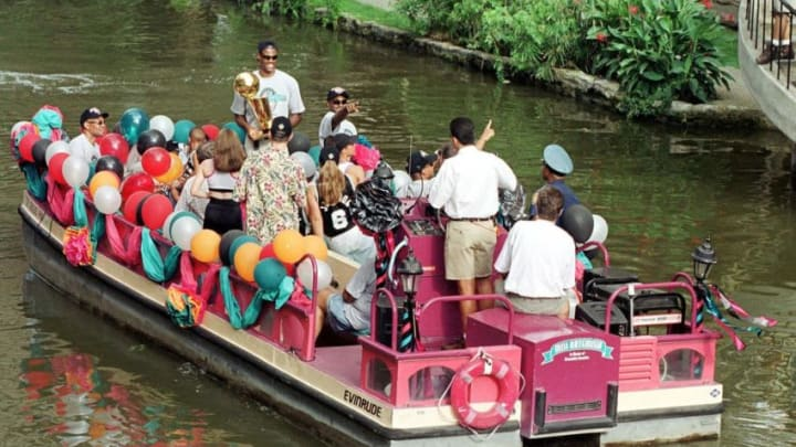 SAN ANTONIO, UNITED STATES: David Robinson of the San Antonio Spurs (with trophy) along with teammates and family members ride a tour barge down the San Antonio River 27 June 1999 as they celebrate their win in the NBA Finals with a river parade. (PAUL BUCK/AFP via Getty Images)