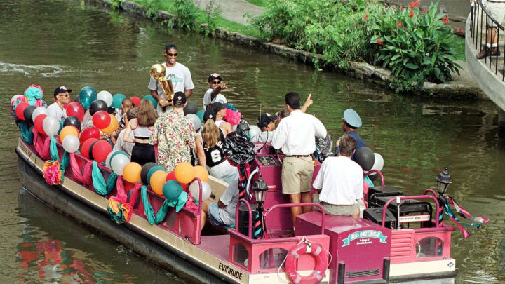 SAN ANTONIO, UNITED STATES: David Robinson of the San Antonio Spurs (with trophy) rides a tour barge down the San Antonio River as they celebrate their win in the NBA Finals on June 27, 1999. (PAUL BUCK/AFP via Getty Images)