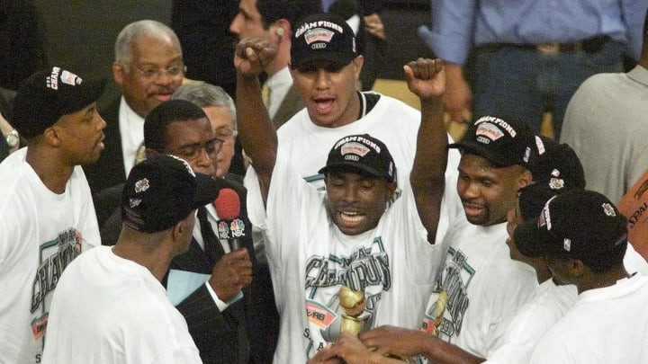 NEW YORK, UNITED STATES: Avery Johnson (C) of the San Antonio Spurs and the rest of team gathers around the championship trophy 25 June, 1999, after the Spurs won game five of the NBA Finals against the New York Knicks (TIMOTHY A. CLARY/AFP via Getty Images)