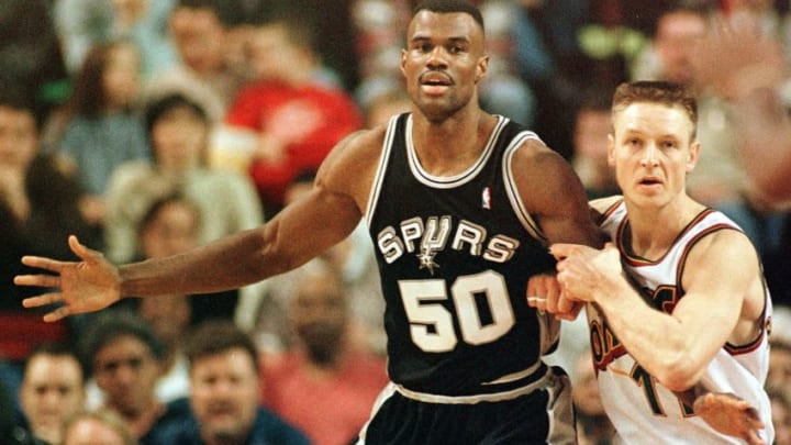 SEATTLE, UNITED STATES: Seattle Supersonic Detlef Schrempf (R) tries to tie up San Antonio Spurs David Robinson (L) during first quarter action of their game in Seattle, WA on 26 February. AFP PHOTO/Dan Levine (Photo credit should read DAN LEVINE/AFP/Getty Images)