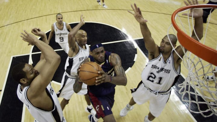 San Antonio, UNITED STATES: LeBron James (C) of the Cleveland Cavaliers drives between Horry (L), Duncan (R) and Bowen (back) of the San Antonio Spurs during Game One of the '07 NBA Finals (JEFF HAYNES/AFP via Getty Images)