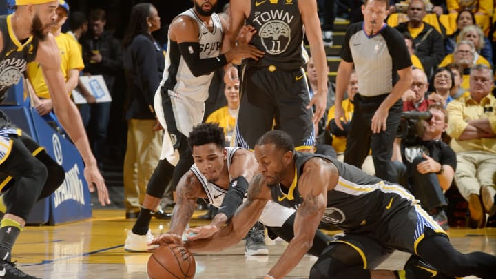 OAKLAND, CA – APRIL 16: Dejounte Murray of the San Antonio Spurs and Andre Iguodala of the Golden State Warriors go after a loose ball in Game 2 of Round 1 of the 2018 NBA Playoffs (Photo by Noah Graham/NBAE via Getty Images)