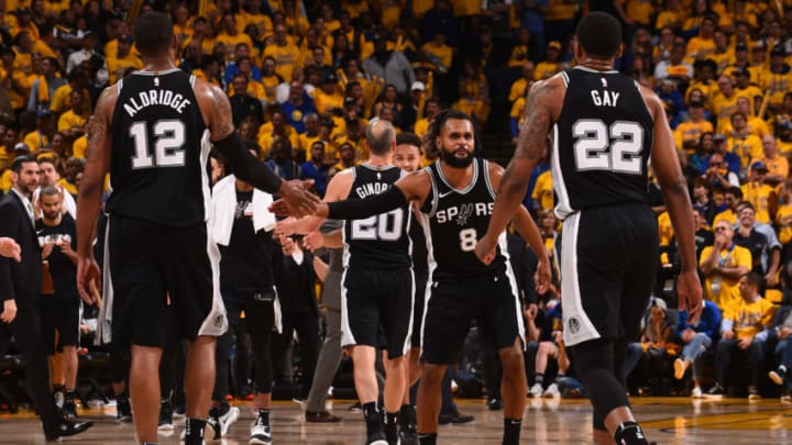 OAKLAND, CA - APRIL 24: LaMarcus Aldridge #12 of the San Antonio Spurs and Patty Mills #8 of the San Antonio Spurs exchange a high give against the Golden State Warriors in Game Five of Round One of the 2018 NBA Playoffs on April 24, 2018 at ORACLE Arena in Oakland, California. NOTE TO USER: User expressly acknowledges and agrees that, by downloading and or using this photograph, user is consenting to the terms and conditions of Getty Images License Agreement. Mandatory Copyright Notice: Copyright 2018 NBAE (Photo by Noah Graham/NBAE via Getty Images)