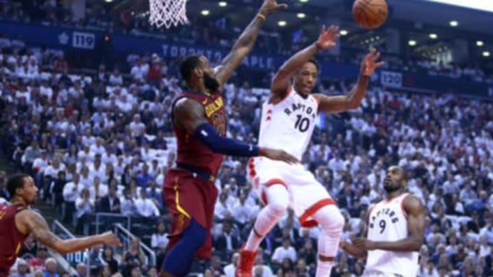 TORONTO, ON – MAY 03: DeMar DeRozan #10 of the Toronto Raptors passes the ball as LeBron James #23 of the Cleveland Cavaliers defends in the first half of Game Two of the Eastern Conference Semifinals during the 2018 NBA Playoffs at Air Canada Centre on May 3, 2018 in Toronto, Canada. NOTE TO USER: User expressly acknowledges and agrees that, by downloading and or using this photograph, User is consenting to the terms and conditions of the Getty Images License Agreement. (Photo by Vaughn Ridley/Getty Images)