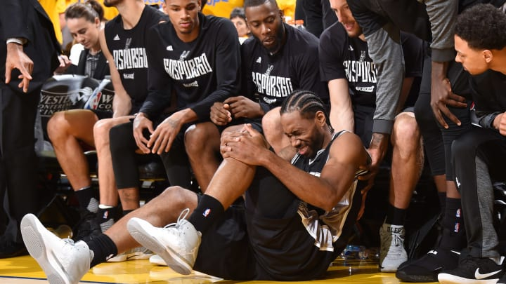 OAKLAND, CA – MAY 14: Kawhi Leonard #2 of the San Antonio Spurs grabs his legs after an injury in Game One of the Western Conference Finals against the Golden State Warriors during the 2017 NBA Playoffs on May 14, 2017 at ORACLE Arena in Oakland, California. (Photo by Andrew D. Bernstein/NBAE via Getty Images)