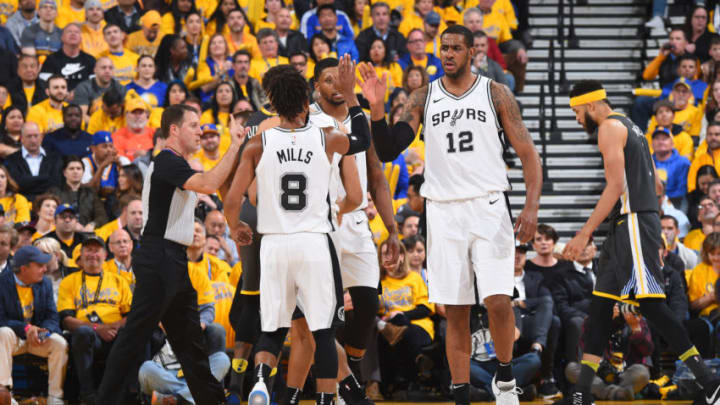 OAKLAND, CA - APRIL 16: LaMarcus Aldridge #12 and Patty Mills #8 of the San Antonio Spurs high five during the game against the Golden State Warriors in Game Two of Round One of the 2018 NBA Playoffs on April 16, 2018 at ORACLE Arena in Oakland, California. NOTE TO USER: User expressly acknowledges and agrees that, by downloading and or using this photograph, user is consenting to the terms and conditions of Getty Images License Agreement. Mandatory Copyright Notice: Copyright 2018 NBAE (Photo by Andrew D. Bernstein/NBAE via Getty Images)