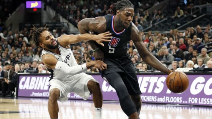 SAN ANTONIO,TX - DECEMBER 18 : Patty Mills #8 of the San Antonio Spurs tries to guard Montrezl Harrell #5 of the Los Angeles Clippers at AT&T Center on December 18, 2017 in San Antonio, Texas. NOTE TO USER: User expressly acknowledges and agrees that , by downloading and or using this photograph, User is consenting to the terms and conditions of the Getty Images License Agreement. (Photo by Ronald Cortes/Getty Images)