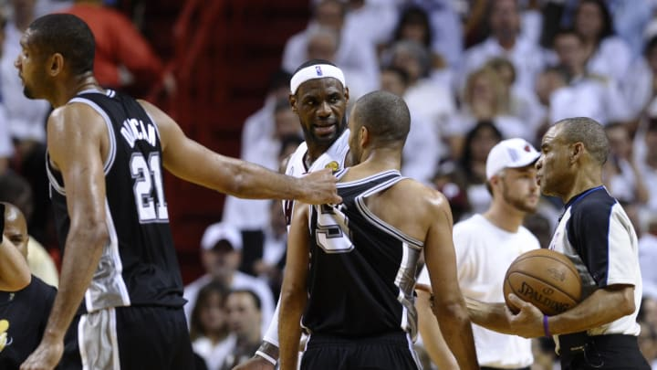 Tim Duncan (L) of the San Antonio Spurs pulls Tony Parker away from the ref as LeBron James of the Miami Heat looks on during Game 7 of the NBA Finals at the American Airlines Arena. (BRENDAN SMIALOWSKI/AFP via Getty Images)