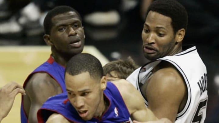 SAN ANTONIO, UNITED STATES: Tayshaun Prince (Front) of the detroit Pistons grabs a rebound in front of team mate Antonio McDyess (L) and Robert of the San Antonio Spurs during game seven of the NBA Finals 23 June, 2005 at the SBC Center in San Antonio, TX. The best of seven series is tied at 3-3 to force a winner take all game seven. AFP PHOTO/ Robert SULLIVAN (Photo credit should read ROBERT SULLIVAN/AFP/Getty Images)