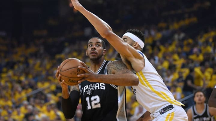 OAKLAND, CA - APRIL 14: LaMarcus Aldridge #12 of the San Antonio Spurs looks to get his shot off over the out stretched arm of JaVale McGee #1 of the Golden State Warriors in the first quarter during Game One of the first round of the 2018 NBA Playoff at ORACLE Arena on April 14, 2018 in Oakland, California. NOTE TO USER: User expressly acknowledges and agrees that, by downloading and or using this photograph, User is consenting to the terms and conditions of the Getty Images License Agreement. (Photo by Thearon W. Henderson/Getty Images)