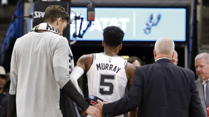 SAN ANTONIO, TX - OCTOBER 7: Dejounte Murray #5 of the San Antonio Spurs walks off the court after being injured on a play as teammate Pau Gasol #16 looks on during a preseason game against the Houston Rockets on October 7, 2018 at the AT&T Center in San Antonio, Texas. NOTE TO USER: User expressly acknowledges and agrees that, by downloading and or using this photograph, User is consenting to the terms and conditions of the Getty Images License Agreement. (Photo by Edward A. Ornelas/Getty Images)
