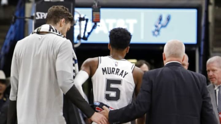 SAN ANTONIO, TX – OCTOBER 7: Dejounte Murray #5 of the San Antonio Spurs walks off the court after being injured on a play as teammate Pau Gasol #16 looks on during a preseason game against the Houston Rockets on October 7, 2018 at the AT&T Center in San Antonio, Texas. NOTE TO USER: User expressly acknowledges and agrees that, by downloading and or using this photograph, User is consenting to the terms and conditions of the Getty Images License Agreement. (Photo by Edward A. Ornelas/Getty Images)