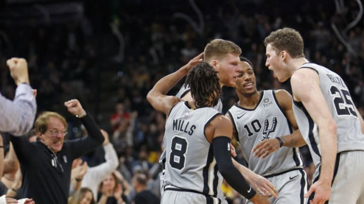SAN ANTONIO, TX - DECEMBER 7: Fans and Davis Bertans #42 of the San Antonio Spurs reacts as he do teammates Patty Mills #8 and DeMar DeRozan #10 and Jakob Poeltl #25 after a three against the Los Angeles Lakers at AT&T Center on December 7 , 2018 in San Antonio, Texas. NOTE TO USER: User expressly acknowledges and agrees that , by downloading and or using this photograph, User is consenting to the terms and conditions of the Getty Images License Agreement. (Photo by Ronald Cortes/Getty Images)