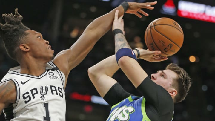 SAN ANTONIO, TX - FEBRUARY 26: Luka Doncic #77 of the Dallas Mavericks pushes the hand away of Lonnie Walker #1 of the San Antonio Spurs as Walker was called for the foul during second-half action at AT&T Center on February 26, 2020 in San Antonio, Texas. The Mavs defeated the Spurs 109-103. NOTE TO USER: User expressly acknowledges and agrees that , by downloading and or using this photograph, User is consenting to the terms and conditions of the Getty Images License Agreement. (Photo by Ronald Cortes/Getty Images)