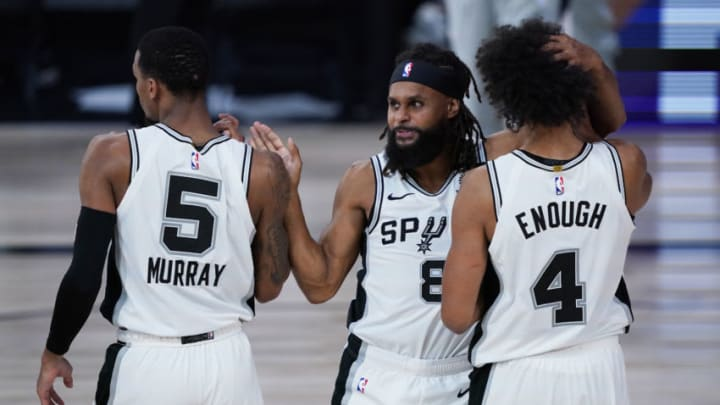LAKE BUENA VISTA, FLORIDA - AUGUST 02: Dejounte Murray #5, Patty Mills #8 and Derrick White #4 of the San Antonio Spurs celebrate a win over the Memphis Grizzlies at Visa Athletic Center at ESPN Wide World Of Sports Complex on August 2, 2020 in Lake Buena Vista, Florida. NOTE TO USER: User expressly acknowledges and agrees that, by downloading and or using this photograph, User is consenting to the terms and conditions of the Getty Images License Agreement. (Photo by Ashley Landis-Pool/Getty Images)