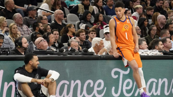 Jan 24, 2020; San Antonio, Texas, USA; Phoenix Suns guard Devin Booker (1) talks with San Antonio Spurs forward Trey Lyles (41) as they wait to enter the game in the first half at AT&T Center. (Scott Wachter-USA TODAY Sports)