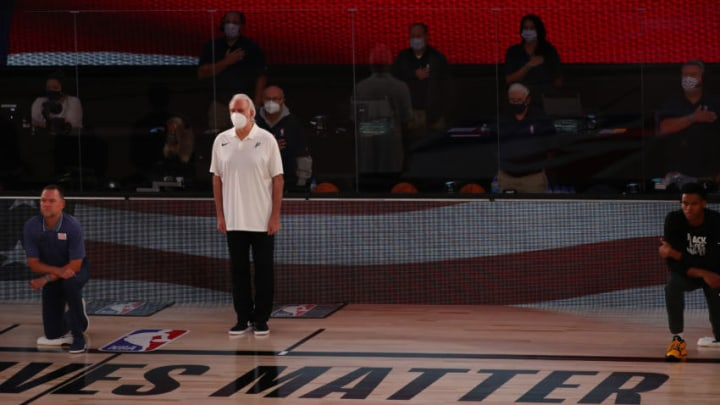 Aug 5, 2020; Lake Buena Vista, Florida, USA; Members of the Denver Nuggets, concluding head coach Michael Malone (left), kneel as San Antonio Spurs head coach Gregg Popovich (middle) stands for the Nation Anthem before the first half on a NBA basketball game at Visa Athletic Center. Mandatory Credit: Kim Klement-USA TODAY Sports