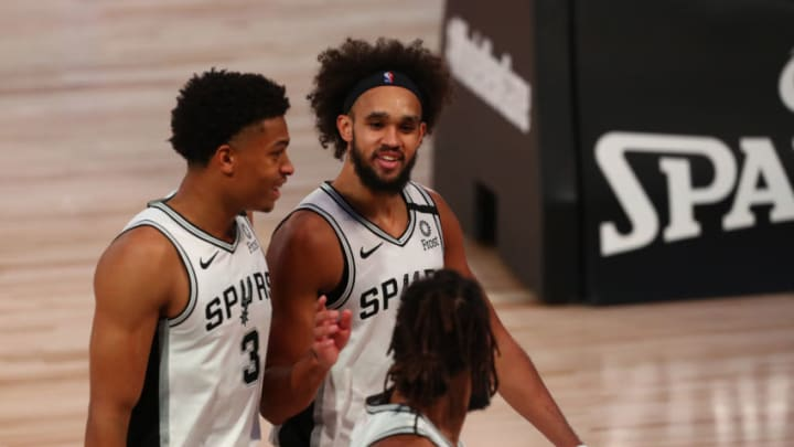 Aug 5, 2020; Lake Buena Vista, Florida, USA; San Antonio Spurs guard Patty Mills (foreground) and forward Keldon Johnson (3) and guard Derrick White (middle) talk as the leave the court at halftime of a NBA basketball game against the Denver Nuggets at Visa Athletic Center. Mandatory Credit: Kim Klement-USA TODAY Sports