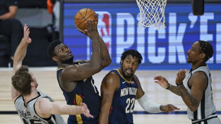 Aug 9, 2020; Lake Buena Vista, Florida, USA; New Orleans Pelicans forward Zion Williamson (middle) with help from teammate Derrick Favors (22) takes a shot as he gets past San Antonio Spurs center Jakob Poeltl (left) during the second half of an NBA basketball game at The Field House. Mandatory Credit: Ashley Landis/Pool Photo-USA TODAY Sports