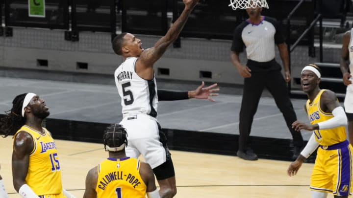 Dec 30, 2020; San Antonio, Texas, USA; San Antonio Spurs guard Dejounte Murray (5) lays in a basket as Los Angeles Lakers forward Montrezl Harrell (15) and guards Kentavious Caldwell-Pope (1) and Dennis Schroder (17) look on in the second quarter at AT&T Center. Mandatory Credit: Scott Wachter-USA TODAY Sports