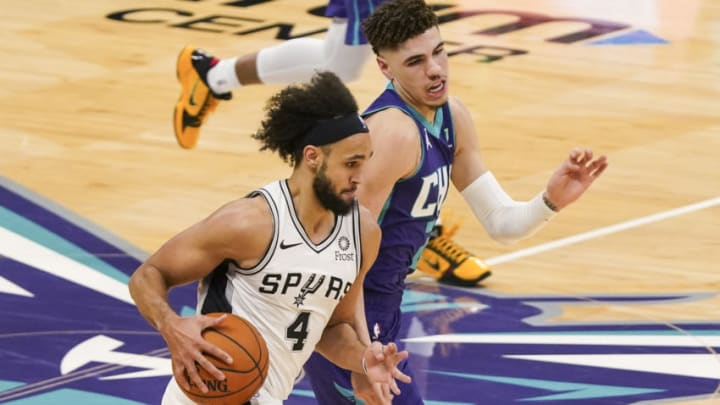 Feb 14, 2021; Charlotte, North Carolina, USA; San Antonio Spurs guard Derrick White (4) brings the ball up court defended by Charlotte Hornets guard LaMelo Ball (2) during the second half at Spectrum Center. Mandatory Credit: Jim Dedmon-USA TODAY Sports