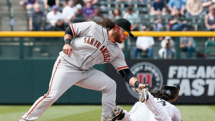 Apr 14, 2016; Denver, CO, USA; Colorado Rockies catcher Tony Wolters (14) loses his helmet sliding to second safely against San Francisco Giants shortstop Brandon Crawford (35) in the fifth inning at Coors Field. Mandatory Credit: Isaiah J. Downing-USA TODAY Sports