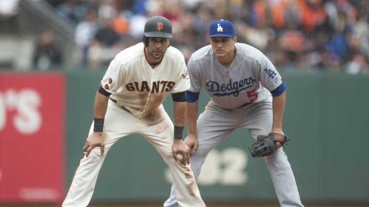 Apr 10, 2016; San Francisco, CA, USA; San Francisco Giants left fielder Angel Pagan (16) is held on base by Los Angeles Dodgers shortstop Corey Seager (5) during the sixth inning at AT&T Park. Mandatory Credit: Kenny Karst-USA TODAY Sports
