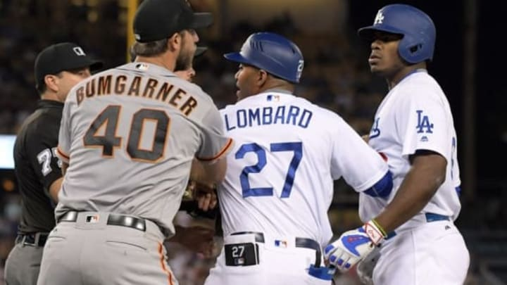 Sep 19, 2016; Los Angeles, CA, USA; San Francisco Giants pitcher Madison Bumgarner (40) and Los Angeles Dodgers right fielder Yasiel Puig (66) are restrained by Dodgers first base coach first base coach George Lomgard (27) during a MLB game at Dodger Stadium. Mandatory Credit: Kirby Lee-USA TODAY Sports