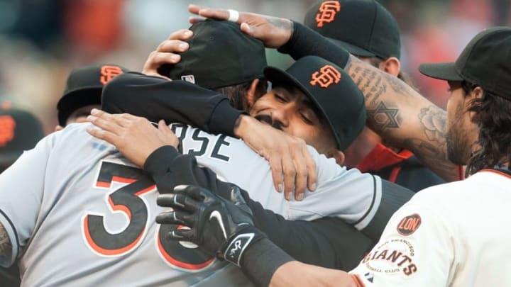 May 7, 2015; San Francisco, CA, USA; San Francisco Giants relief pitcher Sergio Romo (center) hugs Miami Marlins first baseman Michael Morse (38) after Morse received his 2014 World Series ring at AT&T Park. Mandatory Credit: Ed Szczepanski-USA TODAY Sports