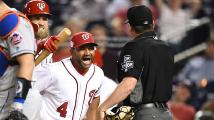 WASHINGTON, DC – SEPTEMBER 20: Manager Dave Martinez #4 of the Washington Nationals holds back Bryce Harper #34 from umpire D.J. Rayburn after getting thrown out in the 12th inning during a baseball game against the New York Mets at Nationals Park on September 20, 2018 in Washington, DC. (Photo by Mitchell Layton/Getty Images)