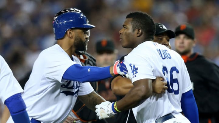 LOS ANGELES, CA - SEPTEMBER 23: Yasiel Puig #66 of the Los Angeles Dodgers is restrained by Matt Kemp #27 and home plate umpire Adrian Johnson after puig was hit by a pitch from Madison Bumgarner of the San Francisco Giants at Dodger Stadium on September 23, 2014 in Los Angeles, California. (Photo by Stephen Dunn/Getty Images)
