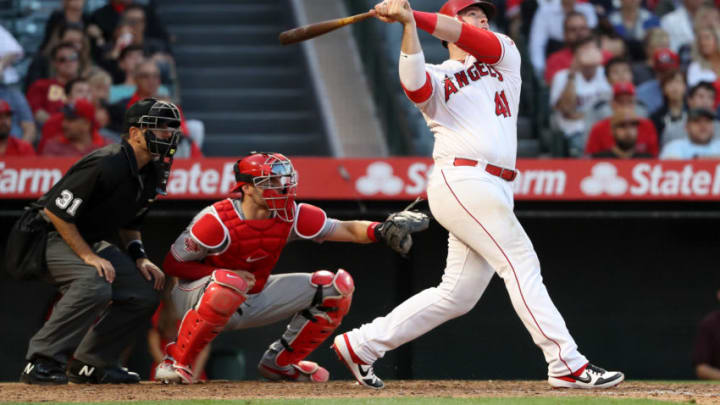 ANAHEIM, CALIFORNIA - JUNE 26: Justin Bour #41 of the Los Angeles Angels of Anaheim reacts after hitting a three-run homerun as umpire Pat Hoberg and Curt Casali #12 of the Cincinnati Reds look on during the eighth inning of a game against the Cincinnati Reds at Angel Stadium of Anaheim on June 26, 2019 in Anaheim, California. (Photo by Sean M. Haffey/Getty Images)