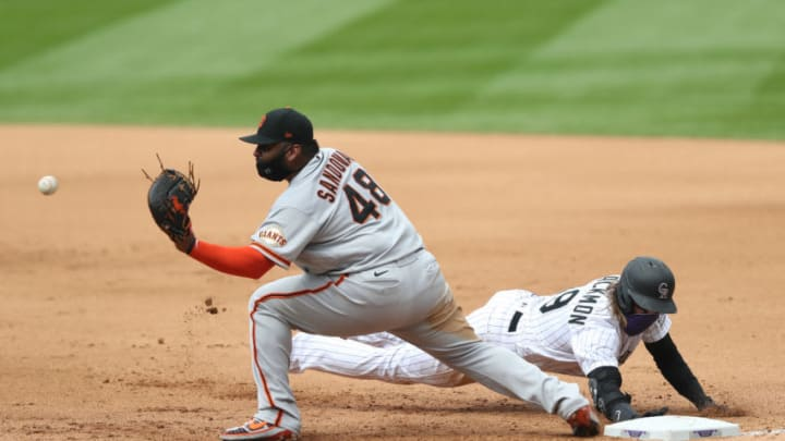 DENVER, COLORADO - AUGUST 06: Charlie Blackmon #19 of the Colorado Rockies beats the throw to first base against Pablo Sandoval #48 of the San Francisco Giants in the fourth inning at Coors Field on August 06, 2020 in Denver, Colorado. (Photo by Matthew Stockman/Getty Images)