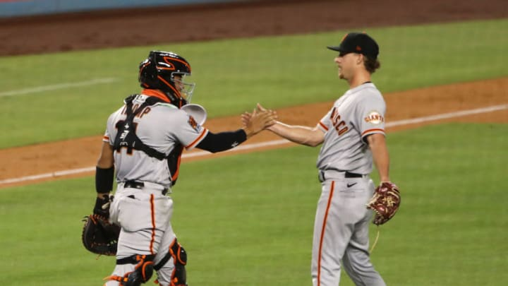LOS ANGELES, CALIFORNIA - AUGUST 08: Chadwick Tromp #14 and Trevor Gott #58 of the San Francisco Giants celebrate their 5-4 win over the Los Angeles Dodgers at Dodger Stadium on August 08, 2020 in Los Angeles, California. (Photo by Katelyn Mulcahy/Getty Images)