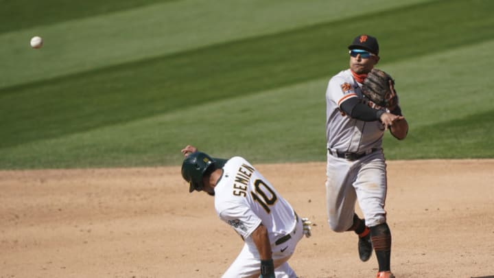 Donovan Solano #7 of the SF Giants completes the double-play throwing over the top of Marcus Semien #10 of the Oakland Athletics in the bottom of the six inning at RingCentral Coliseum on September 19, 2020. (Photo by Thearon W. Henderson/Getty Images)