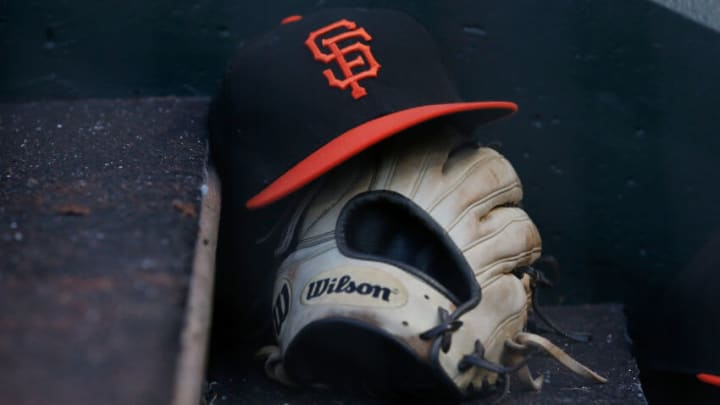 SAN FRANCISCO, CALIFORNIA - JUNE 26: A detail shot of a San Francisco Giants hat and glove in the dugout during the game against the Oakland Athletics at Oracle Park on June 26, 2021 in San Francisco, California. (Photo by Lachlan Cunningham/Getty Images)