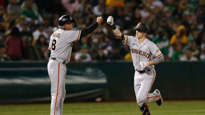 OAKLAND, CALIFORNIA - AUGUST 20: Mike Yastrzemski #5 of the San Francisco Giants celebrates with third base coach Mark Kotsay #7 after hitting a solo home run in the top of the fifth inning against the Oakland Athletics at RingCentral Coliseum on August 20, 2021 in Oakland, California. (Photo by Lachlan Cunningham/Getty Images)