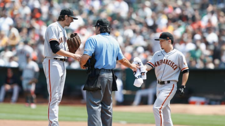 OAKLAND, CALIFORNIA - AUGUST 21: Starting pitcher Kevin Gausman #34 of the San Francisco Giants talks to home plate umpire Phil Cuzzi #10 before pitching in the bottom of the second inning against the Oakland Athletics at RingCentral Coliseum on August 21, 2021 in Oakland, California. (Photo by Lachlan Cunningham/Getty Images)