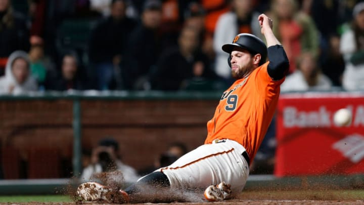 SAN FRANCISCO, CA - APRIL 14: Brandon Belt #9 of the San Francisco Giants slides into home plate to score in the seventh inning against the Colorado Rockies at AT&T Park on April 14, 2017 in San Francisco, California. (Photo by Lachlan Cunningham/Getty Images)