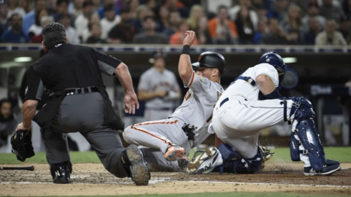 SAN DIEGO, CA - APRIL 14: Joe Panik #12 of the San Francisco Giants is tagged out at the plate by A.J. Ellis #17 of the San Diego Padres during the seventh inning of a baseball game at PETCO Park on April 14, 2018 in San Diego, California. (Photo by Denis Poroy/Getty Images)